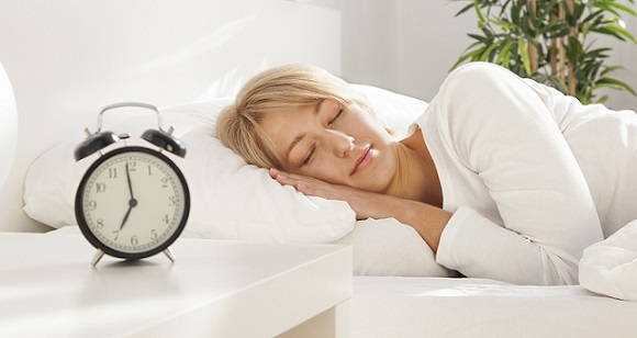 beautiful girl sleeping in her bed. clock on the nightstand. focus on face